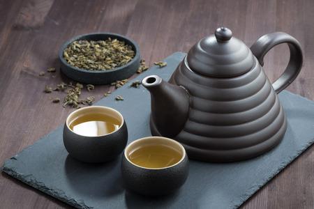 freshly brewed green tea in ceramic ware on wooden table, horizontal
