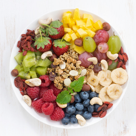 berries, fruits, nuts and granola, products for a delicious healthy breakfast, top view, close-up
