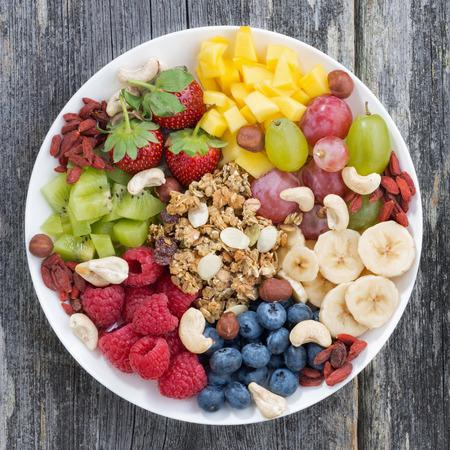 bayas, frutas, nueces y granola, productos para un desayuno saludable, ver arriba, primer plano Foto de archivo