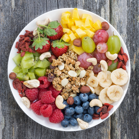 Beeren, Früchte, Nüsse und Müsli, Produkte für ein gesundes Frühstück, Ansicht von oben, close-up