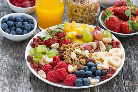 breakfast table: ingredients for a healthy breakfast - berries, fruit and muesli on wooden table, close-up Stock Photo