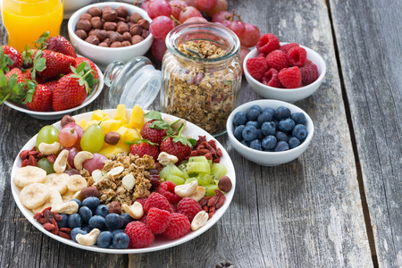 nuts: ingredients for a healthy breakfast - berries, fruit, muesli and wooden background, top view, horizontal