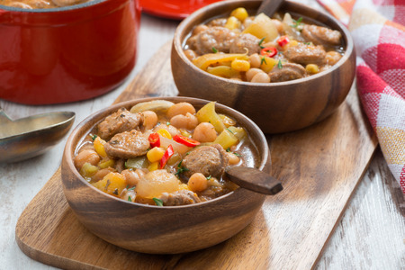 salsa de tomate: menestra de verduras con salchichas en un cuenco de madera a bordo, primer plano