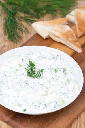 tzatziki: yoghurt sauce tzatziki with herbs, cucumber and garlic, vertical, top view