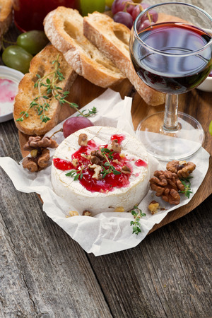 camembert: delicious appetizers for wine - camembert, berry jam, toast and fresh grapes, vertical, top view