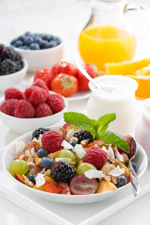 fruit salad in a bowl and various yoghurt, vertical, close-up photo