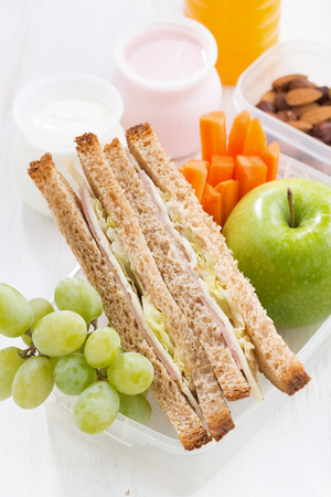 healthy product: school lunch with sandwich on white wooden table, vertical, close-up