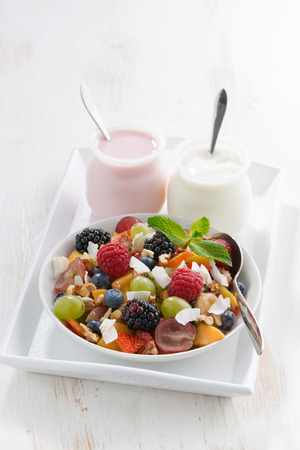 fruit salad and various yoghurt on a white wooden table, vertical, close-up photo