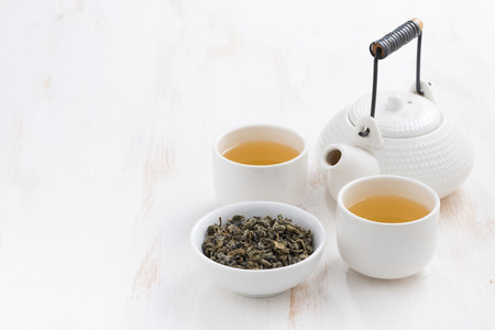 teapot and cups of green tea on a white wooden background, horizontal Stock Photo