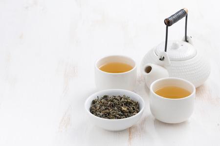 ceremonia: tetera y tazas de té verde sobre un fondo de madera blanca, horizontal