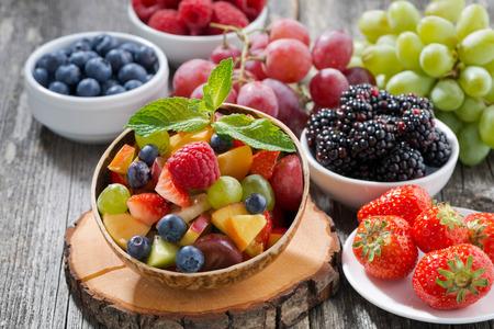 vida sana: ensalada de frutas en un recipiente de bambú y bayas frescas, horizontal