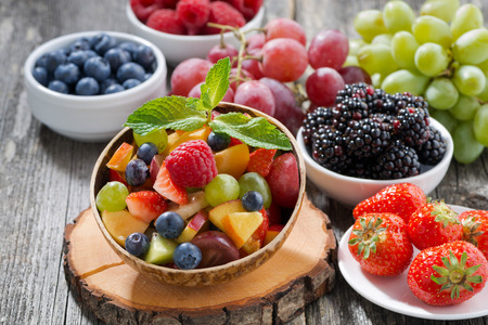 nut: fruit salad in a bamboo bowl and fresh berries, horizontal