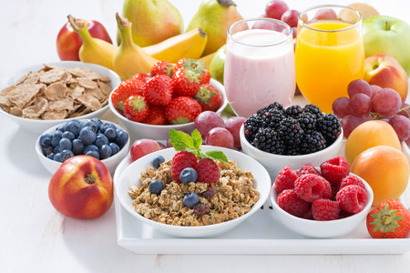eating breakfast: Delicious and healthy breakfast with fruits, berries and cereal on wooden tray