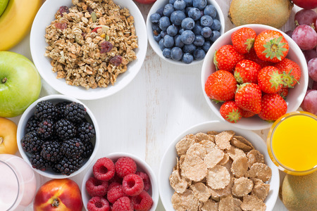 fresh berries, fruit and muesli for breakfast on white table, top view