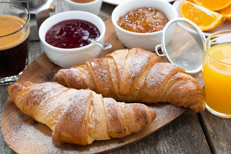 continental breakfast: delicious breakfast with fresh croissants on wooden table, close-up