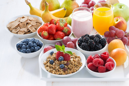Delicious and healthy breakfast with fruits, berries and cereal on wooden tray