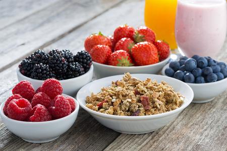 comiendo cereal: desayuno saludable con bayas en el fondo de madera, primer plano, horizontal Foto de archivo