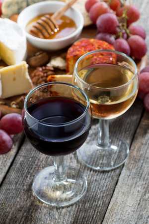 glass of white and red wines, appetizers on a wooden table, vertical, top view