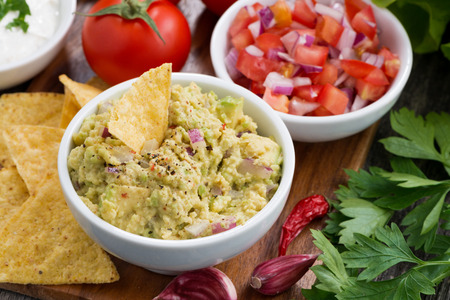 chips and salsa: guacamole sauce, tomato salsa and corn chips, top view, closeup Stock Photo