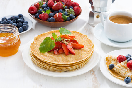 jams: crepes with strawberry, jams and honey on white table, close-up Stock Photo