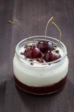 cereza: dessert with cream and cherry jam on dark wooden background, vertical