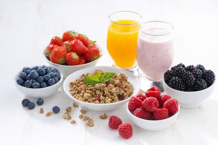 frutilla: bayas frescas, granola, zumo y yogur en un fondo de madera blanco, horizontal