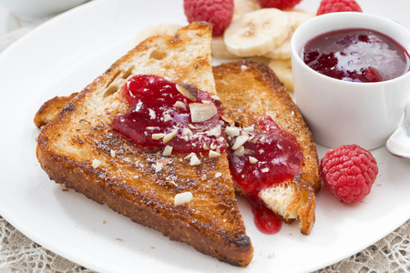 traditionally french: sweet breakfast - toasts with raspberries, banana and jam on plate, close-up, top view
