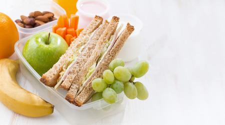botanas: almuerzo escolar con sándwiches y fruta en el fondo blanco, primer plano Foto de archivo