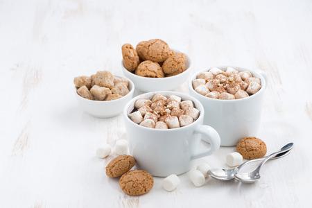 galletas de navidad: dos tazas de chocolate aromatizado con malvaviscos y galletas en el fondo blanco, vista desde arriba