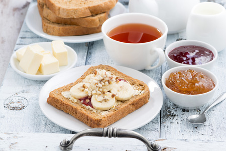 toast with peanut butter and banana, fresh black tea, horizontal Standard-Bild