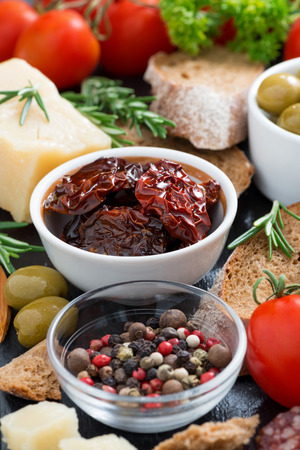 sundried: sun-dried tomatoes in a bowl and various appetizers, vertical, close-up