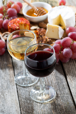 glass of white and red wines, appetizers on a wooden background, vertical, top view