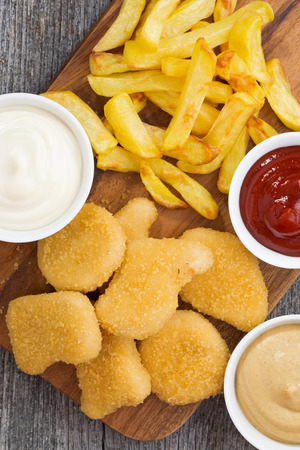 chicken nuggets with french fries and different sauces on wooden board, top view, closeup, vertical Reklamní fotografie