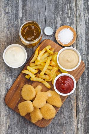 pollo: nuggets de pollo con papas fritas, salsas diferentes y un vaso de cerveza, vista desde arriba, vertical,