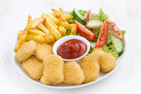 chicken nuggets: chicken nuggets, french fries and vegetable salad, closeup Stock Photo