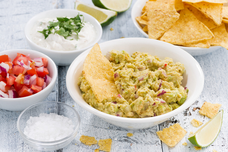 corn chips: spicy avocado sauce and assorted sauces with corn chips, horizontal