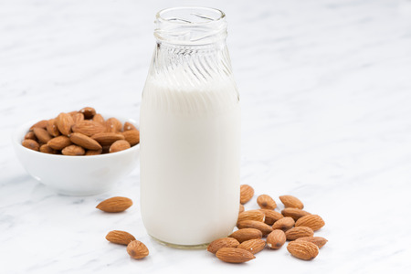 glass bottle: almond milk in a glass bottle on white table, closeup, horizontal