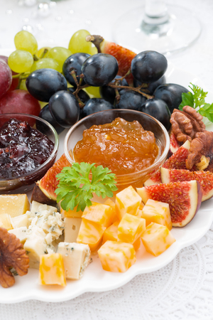 obstteller: delicious cheese and fruit plate to the holiday, closeup vertical, top view Lizenzfreie Bilder