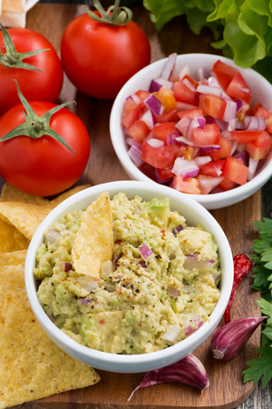 corn chips: guacamole sauce, tomato salsa and corn chips, vertical, closeup