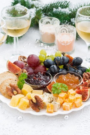 holiday catering: delicacy cheese and fruit plate to the holiday on table, vertical
