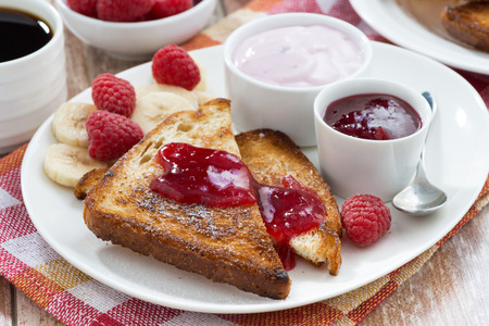 breakfast plate: sweet toasts with fresh raspberry, jam and yoghurt for breakfast, close-up