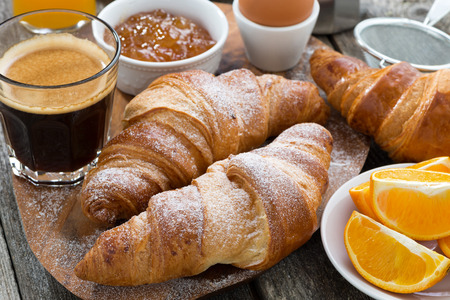 continental breakfast: breakfast with fresh croissants on wooden table, close-up