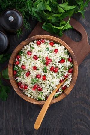 Cauliflower couscous with herbs and pomegranate, top view, vertical, closeup