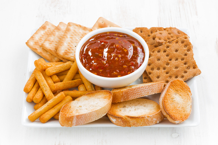 sweet and sour: assortment breads, crackers and sweet, sour tomato sauce, closeup