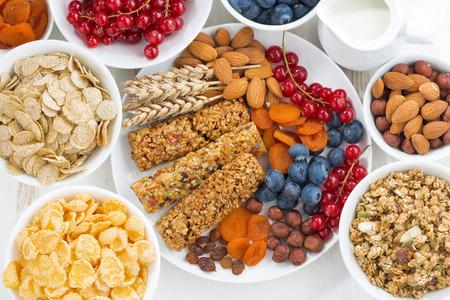 cereales: surtido de barras de cereales muesli, frutas frescas y secas para el desayuno, vista desde arriba, horizontal