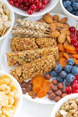 vertical bars: assortment of cereal muesli bars, fresh and dried fruit on plate for breakfast, vertical
