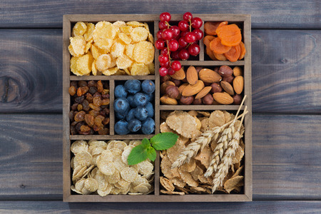 cereal box: breakfast cereal, dried fruit, berries and nuts in a wooden box, top view, horizontal