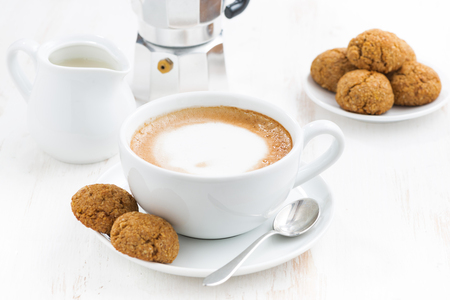 fresh bakery: cup of cappuccino and macaroons on white table, horizontal