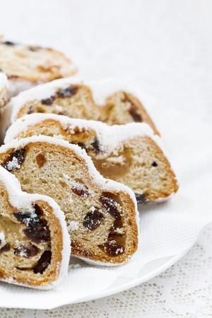 stollen: Christmas Stollen with marzipan on a plate, vertical, closeup