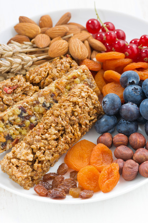 vertical bars: cereal muesli bars, fresh and dried fruit on a plate, closeup vertical, top view